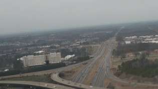 aerial of busy three layer overlapping highway with buildings visible in the distance