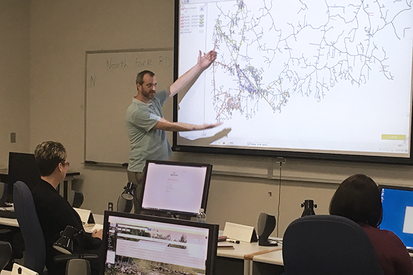 Kevin Hart gesturing to a large screen projection of a map diagram for a TIMS class