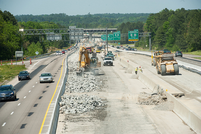 A tractor disturbs the concrete of a construction site in the center of an active NC highway