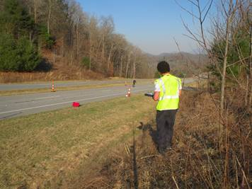 A researcher in a yellow safety vest stands on the edge of a four lane road