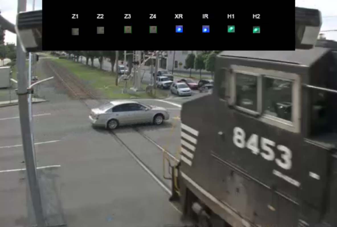 Near collision between freight engine and vehicle trespassing as gates descend