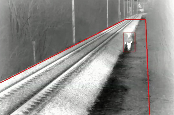 greyscale thermal of figure walking beside railway track with red flagging zones