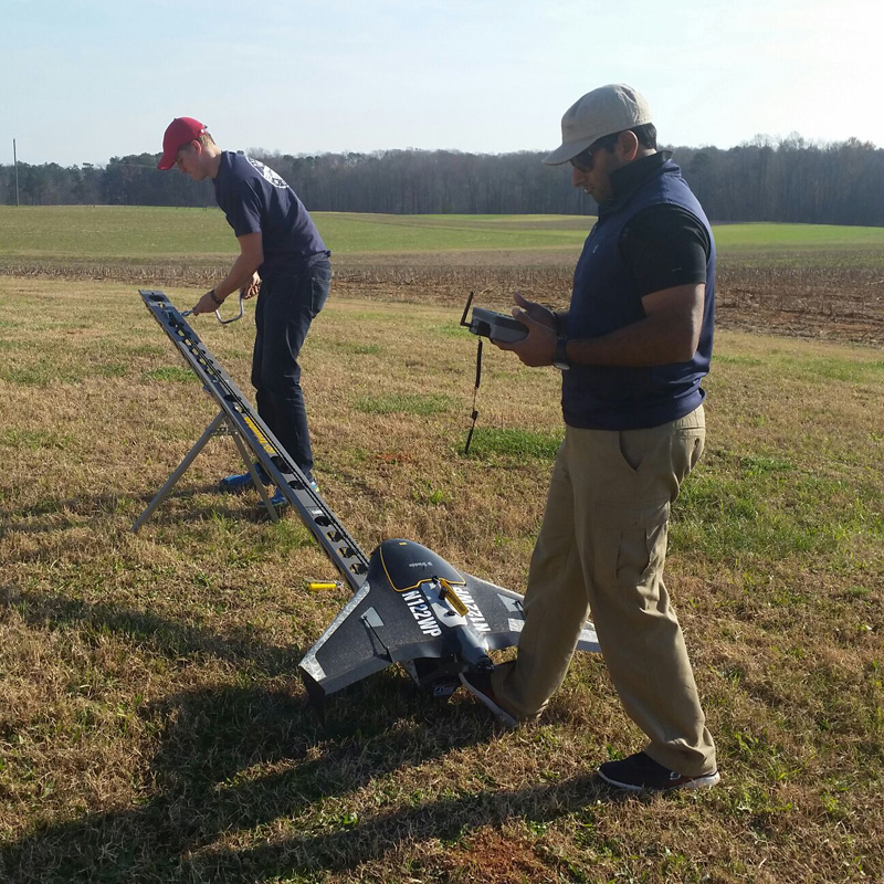 Two men prepare to launch a winged UAS on a long angled launch ramp