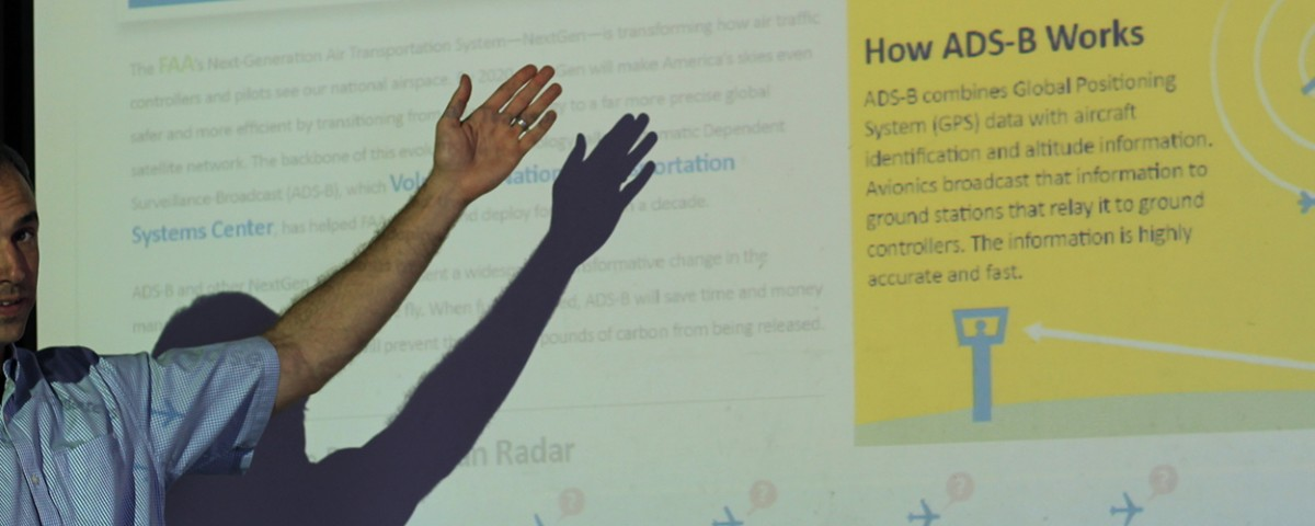 Kyle Snyder gestures to projected presentation on ADS-B aircraft communications