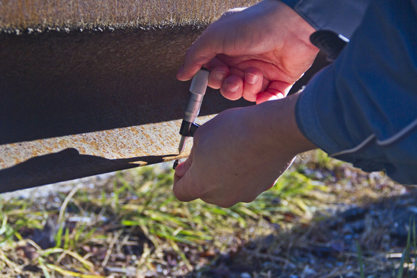 Hands placing a metal bolt in a railway track