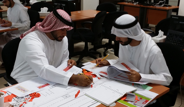 two men wearing Ghutrah style head scarves place orange markers on a diagram of a road