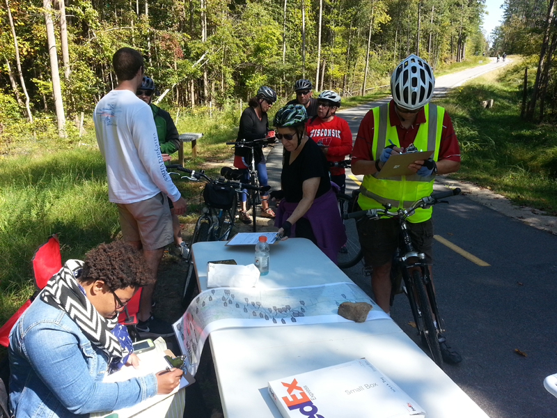 Volunteers and cyclists gathered around data monitoring table