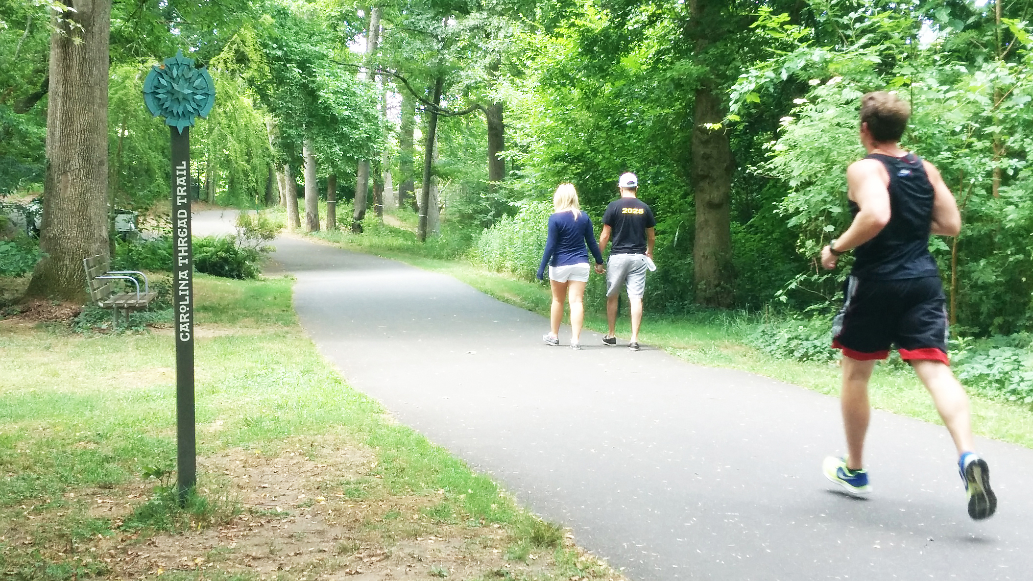 """jogger and walkers pass the """"Carolina Thread Trail"""" marker of a tree lined greenway"""