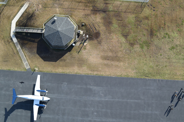 Top-down view of small plane on a landing strip with visible airport command tower