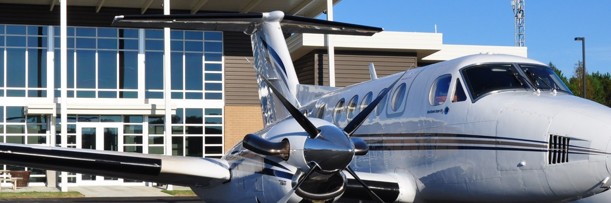 NC Airports Association image of a two engine aircraft in front of an airport building