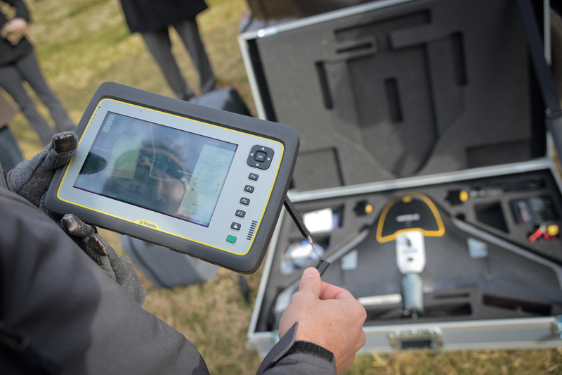man looks at a tablet with drone information over a drone packed up with accessories in a briefcase