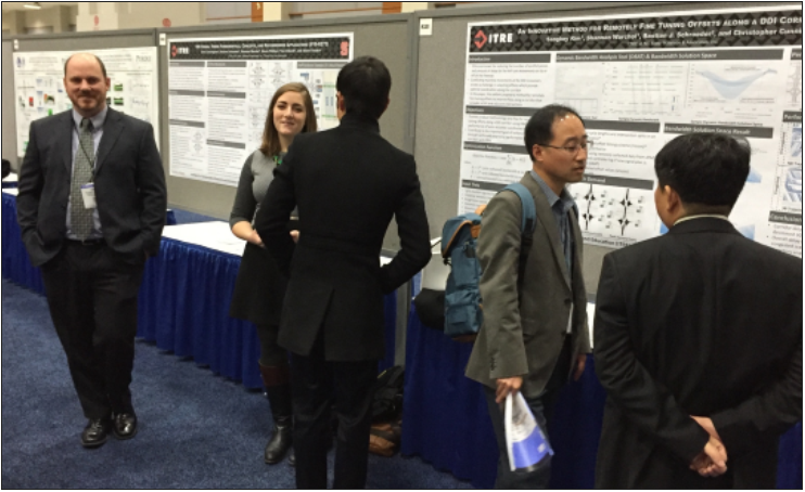 ITRE staff converse with business professionals in front of their research posters and exhibit tables