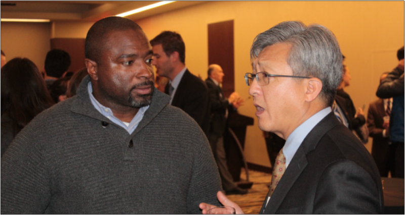 Two men in conversation at a conference, with business professionals visible in the background