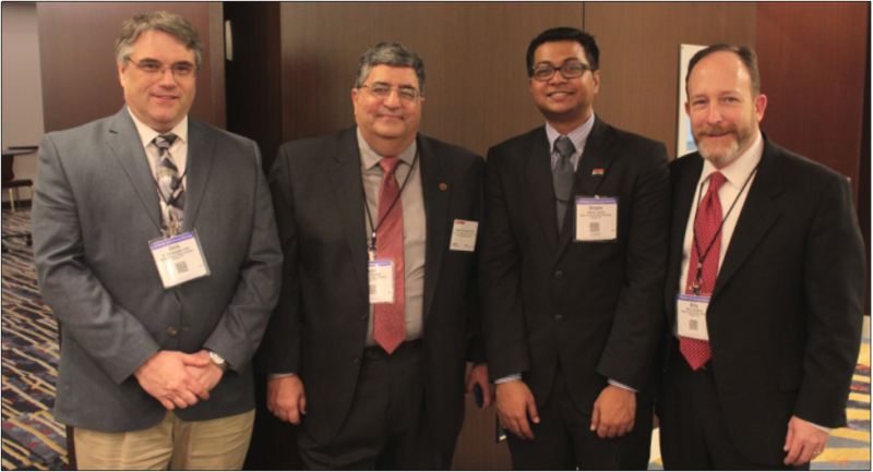 Four men in suits with name tags pose in front of a conference room wall, including Nagui and Shams