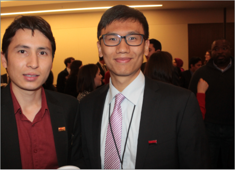 two men in suits pose at a conference, with other business professionals visible in the background