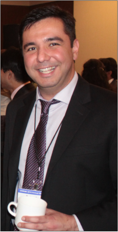Behzad smiling in a suit at a conference, with other business professionals obscured but visible in the background