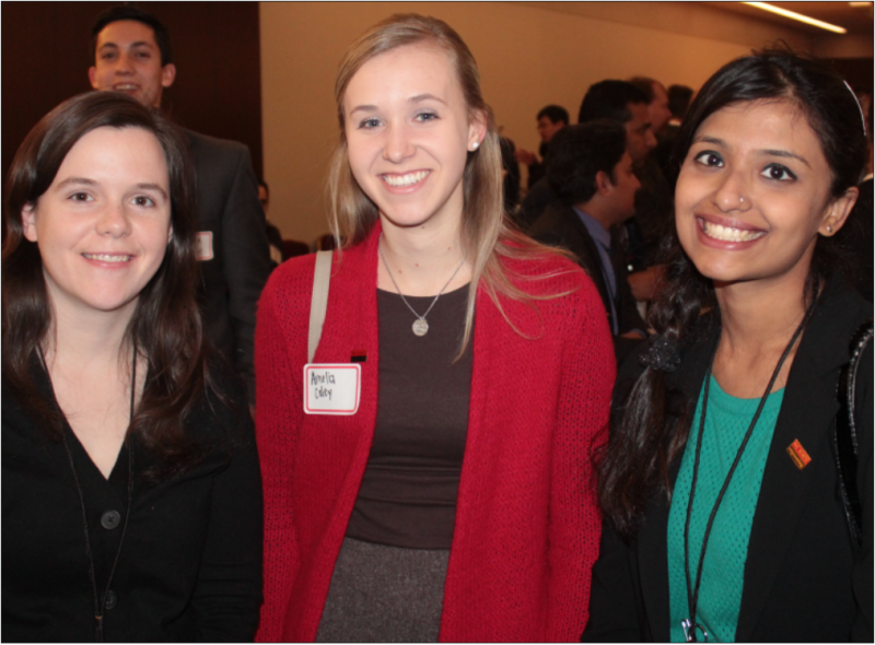 Three smiling women at a conference, with other business professionals in the background