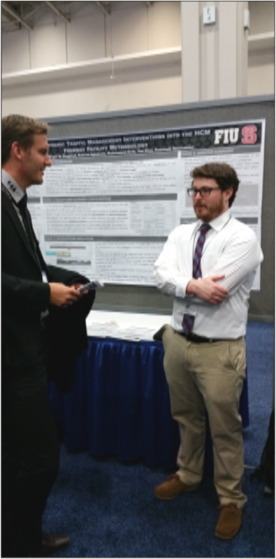 Two men in suits stand in front of an ITRE research poster