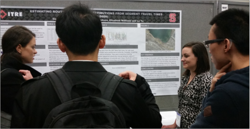 business professionals view a poster displaying ITRE research