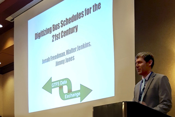 "ITRE research assistant Jonah Freedman, presenting at the NC Public Transportation Association conference, with a projector presentation showing that reads ""Digitizing bus schedules for the 21st century. Jonah Freedman, Walter Jenkins, Jimmy Jones"""