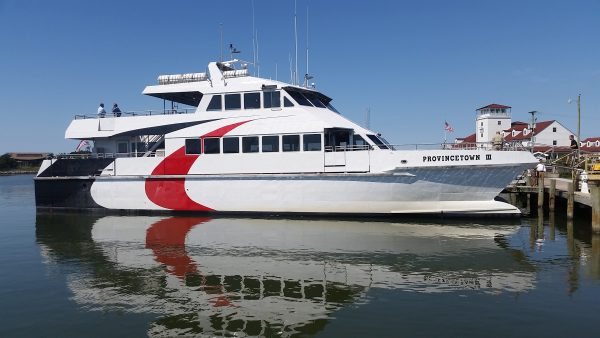 "A ferry named ""Provincetown III"" sits parked at a wooden dock"