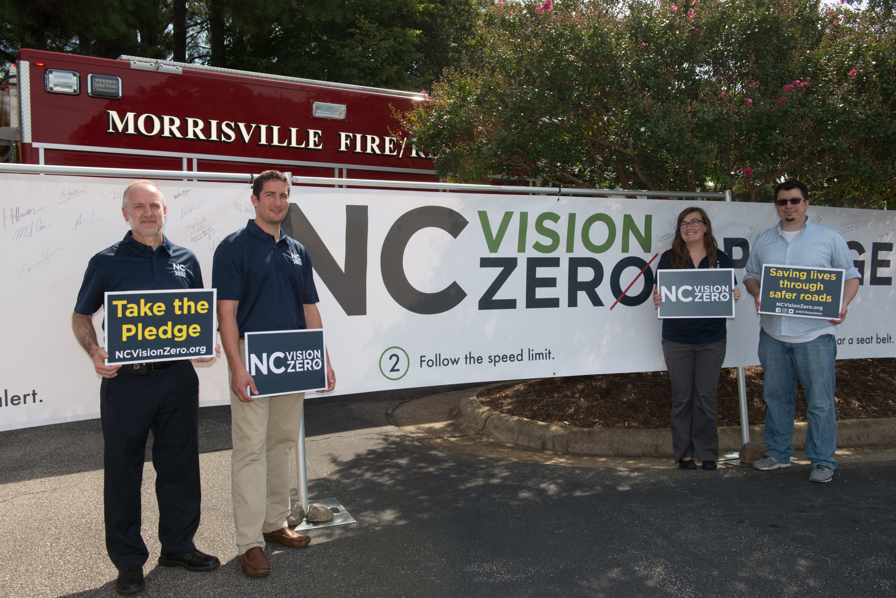 "ITRE researchers stand before an NC Vision Zero banner and a Morrisville firetruck, holding signs that read ""Take The Pledge, ncvisionzero.org"" and ""save lives through safer roads"""