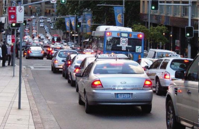 cars stopped in bumper to bumper traffic on a downtown city road