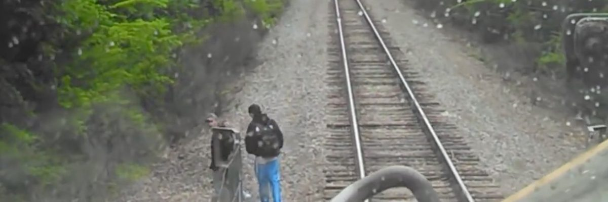 man walking close to railway track in front of an oncoming train