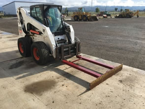 Modified skid steer with a bull blade and a scraper.