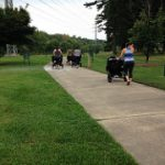 women jogging while pushing strollers along a sidewalk style greenway path